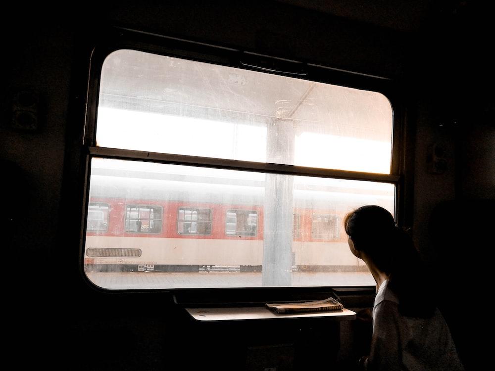 woman standing beside window panel