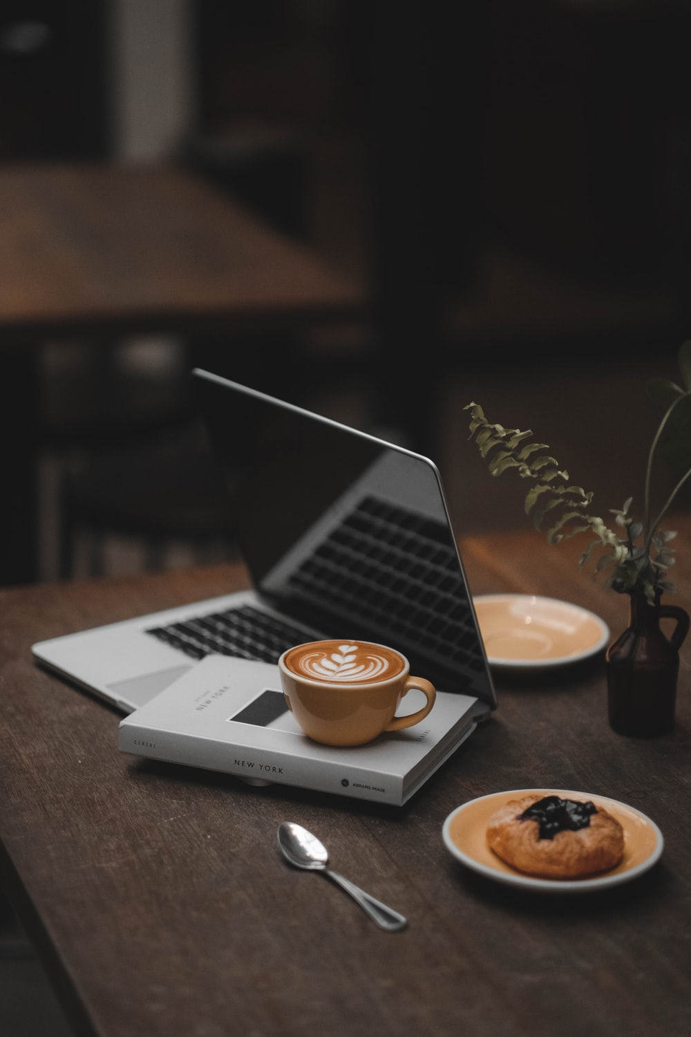 laptop displaying black screen beside latte art mug on book