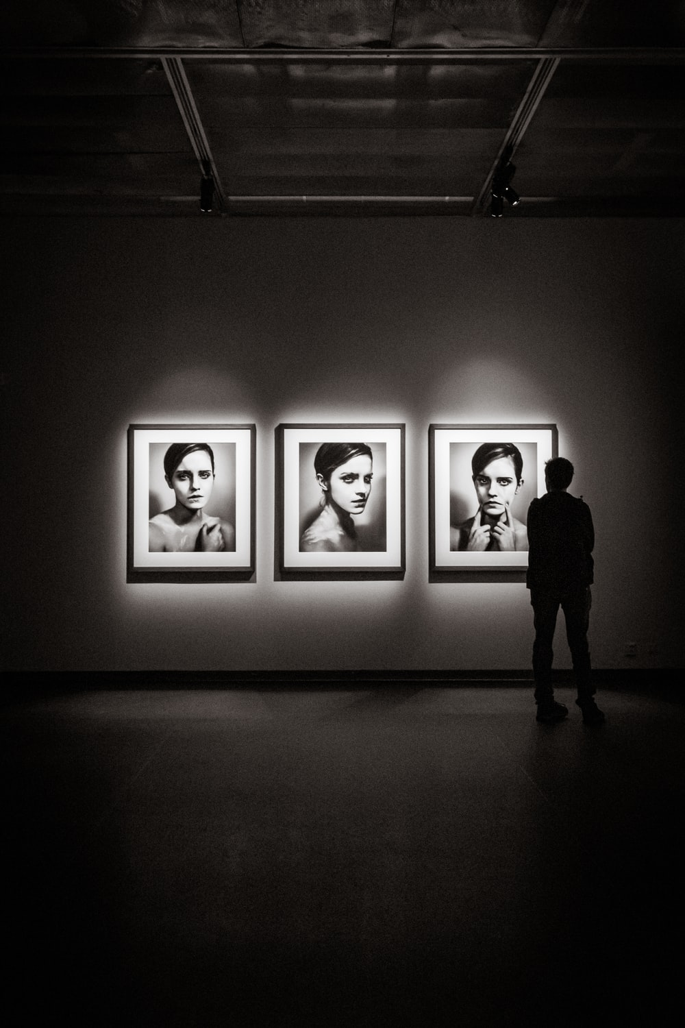 man looking at portraits