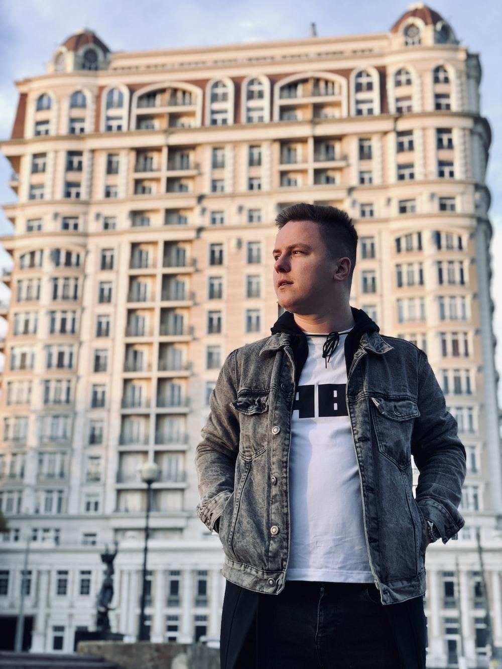 man stands near building