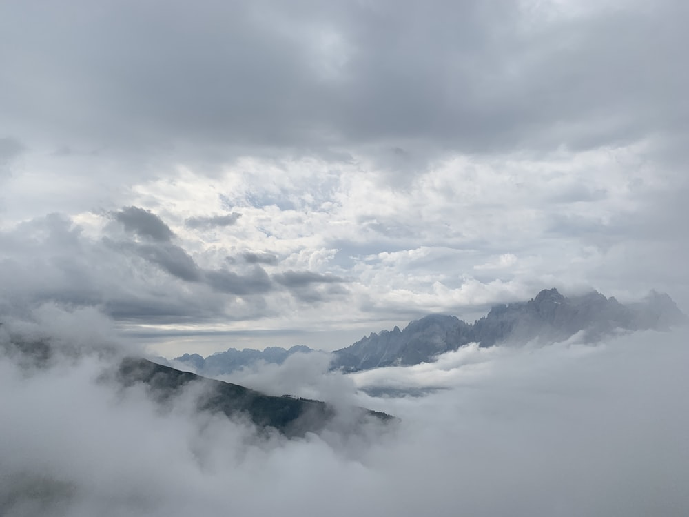 photography of mountain range covering by white clouds during daytime