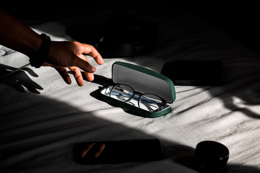 person about to hold black-framed eyeglasses in case