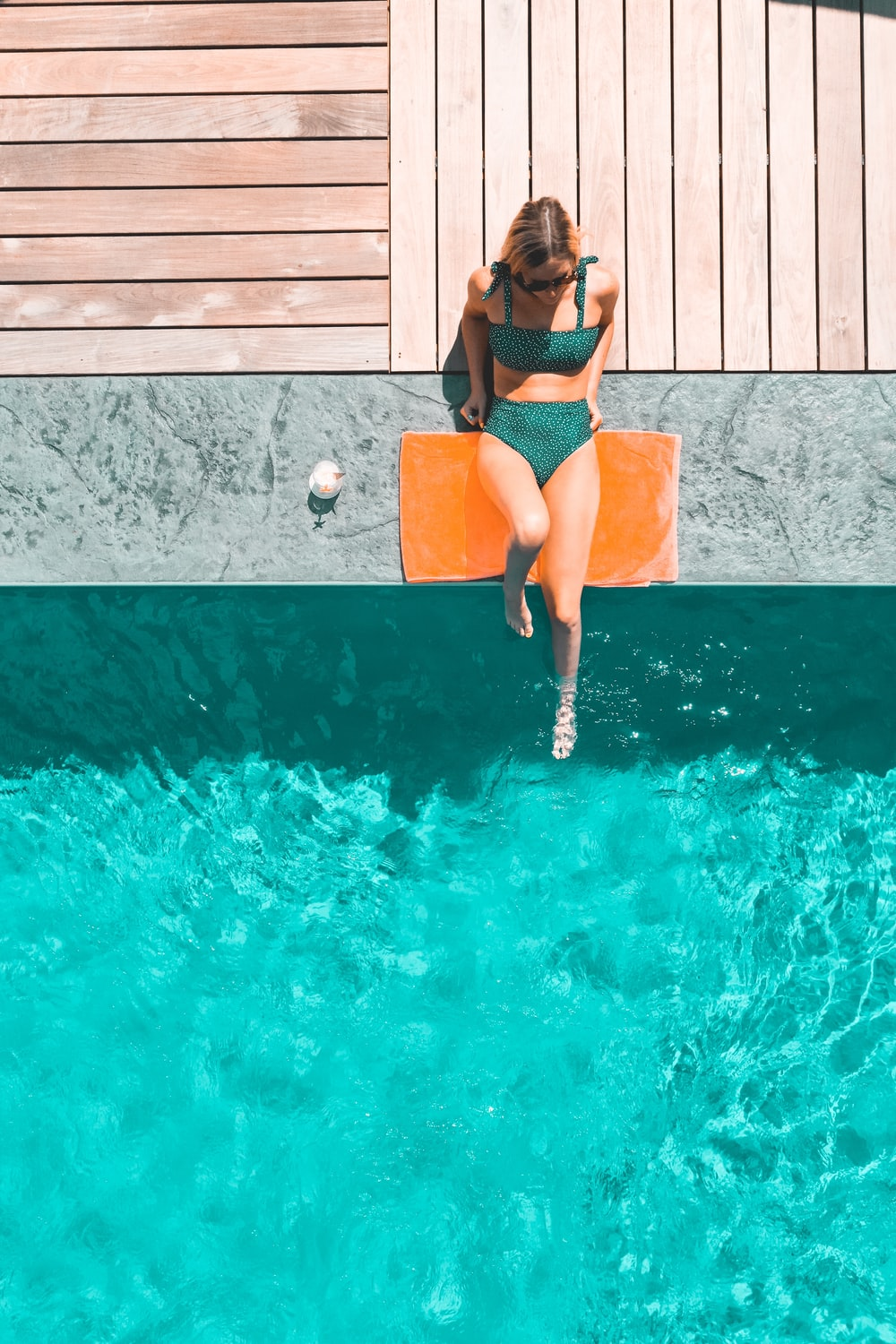 woman lying beside swimming pool during daytime