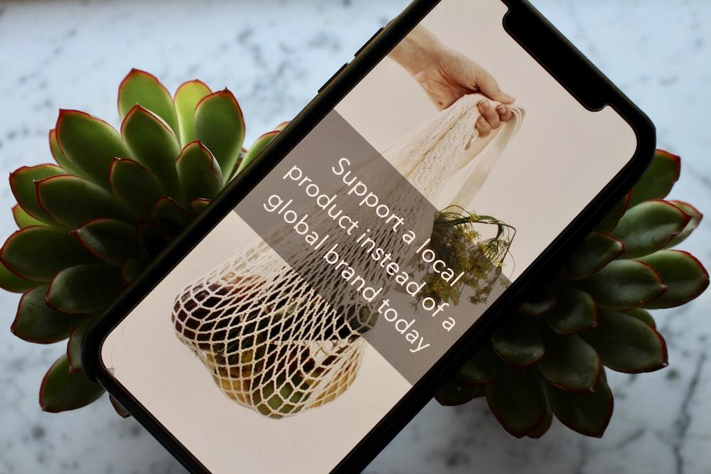 black smartphone on plant