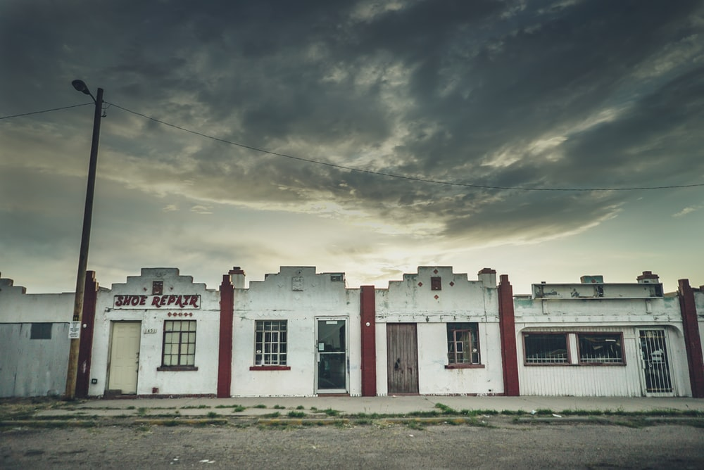 white and red concrete houses under gray skies during daytime