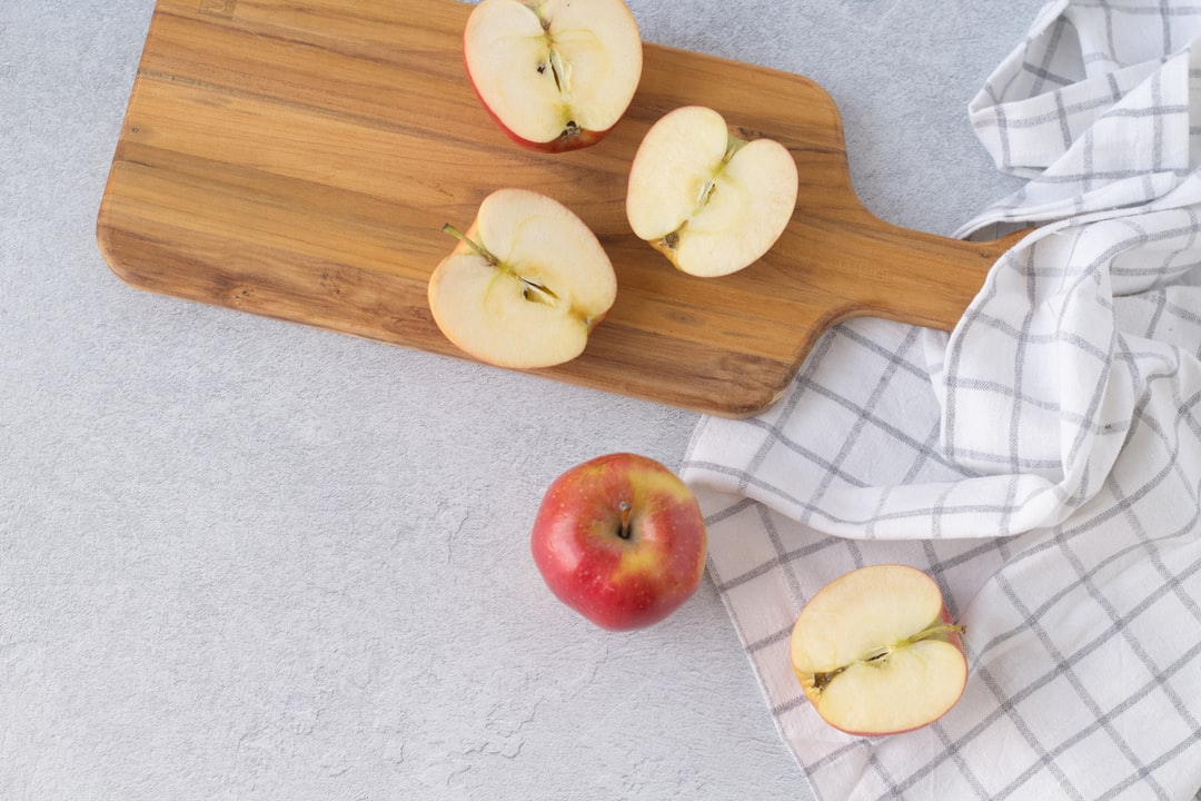 Fall harvest red apples in kitchen with wood cutting board and white dish towel napkin food photography flat lay.