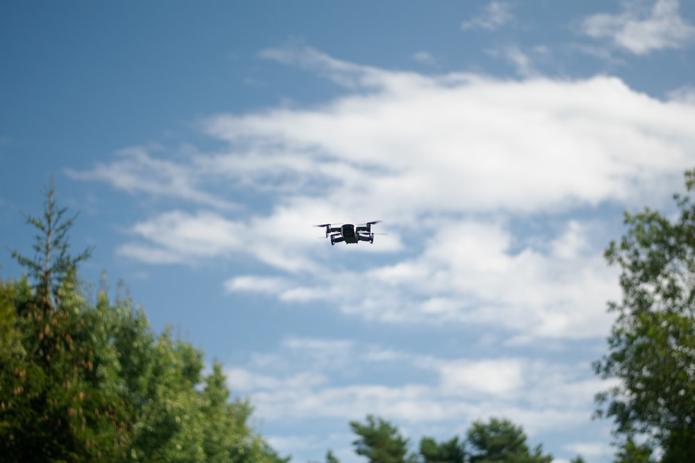 black drone quadcopter on focus photography