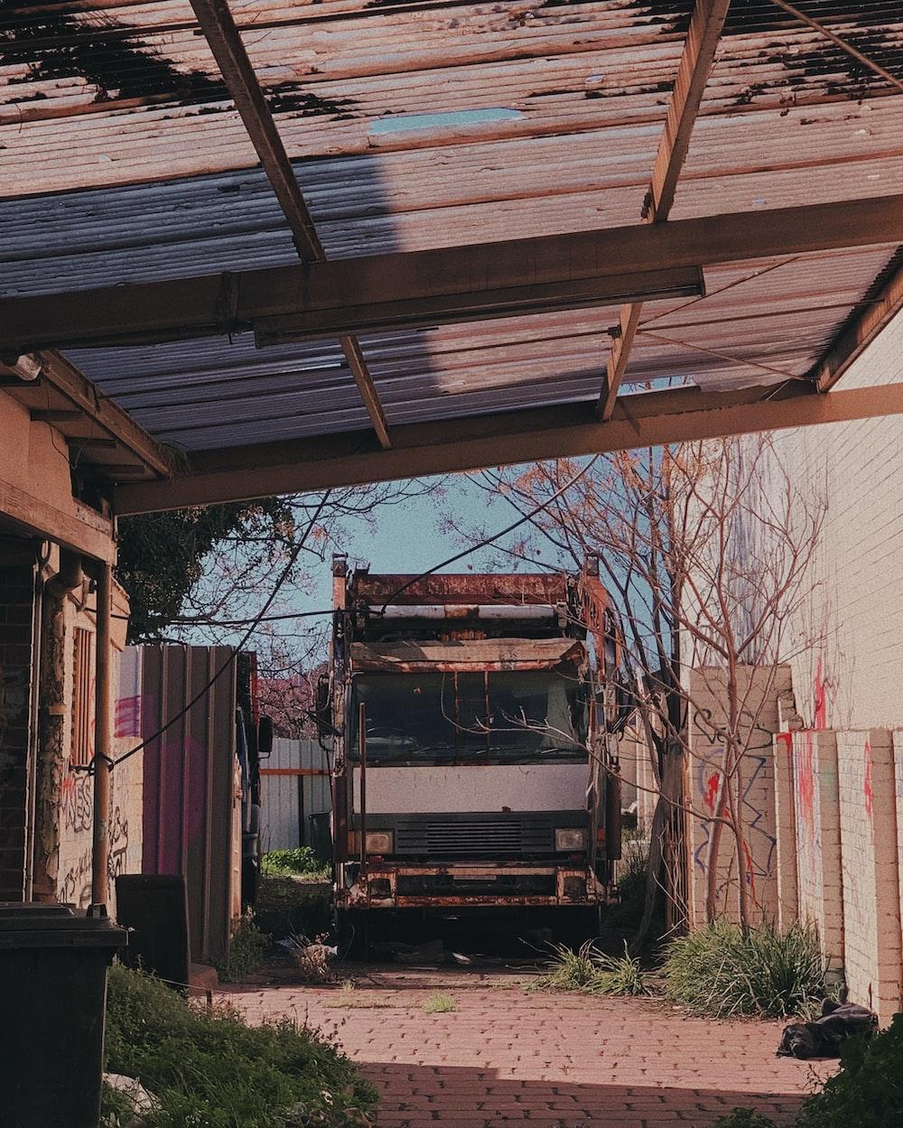 wrecked white vehicle on garage at daytime