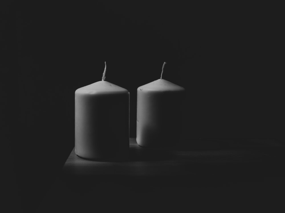 grayscale photography of two pillar candles