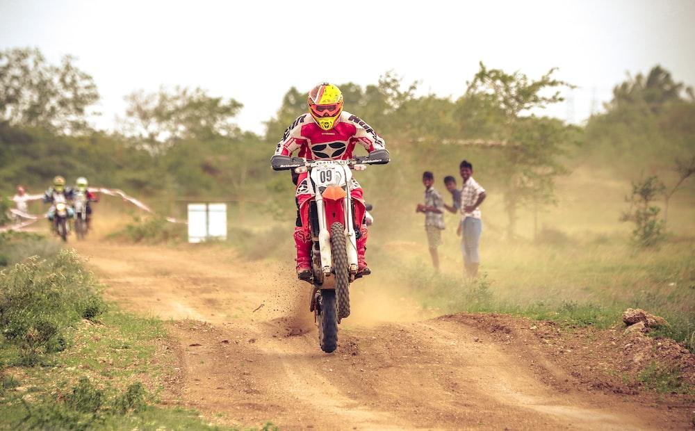 man riding on dirt bike racing on dirt road