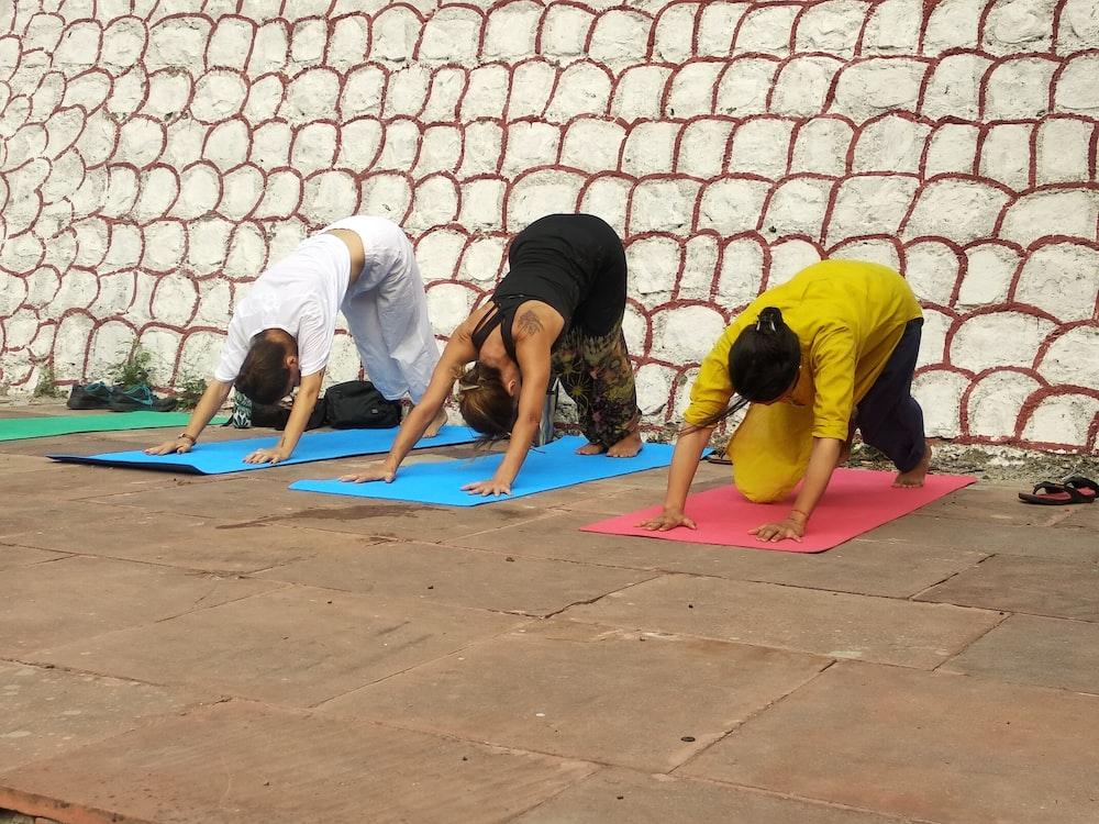 three people doing yoga poses