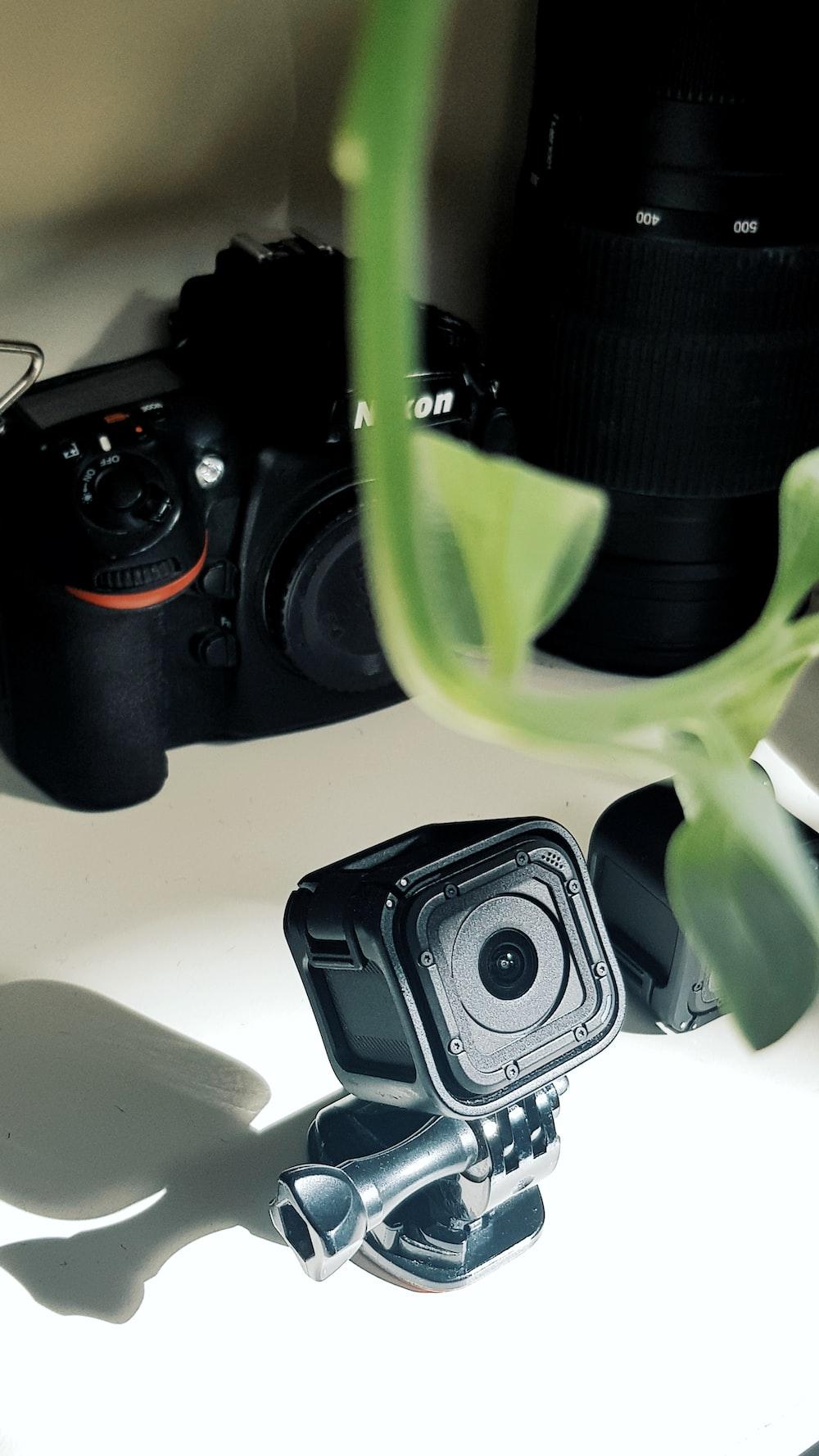 black action camera near Nikon camera