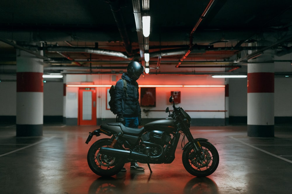 man standing beside a motorcycle in a parking lot