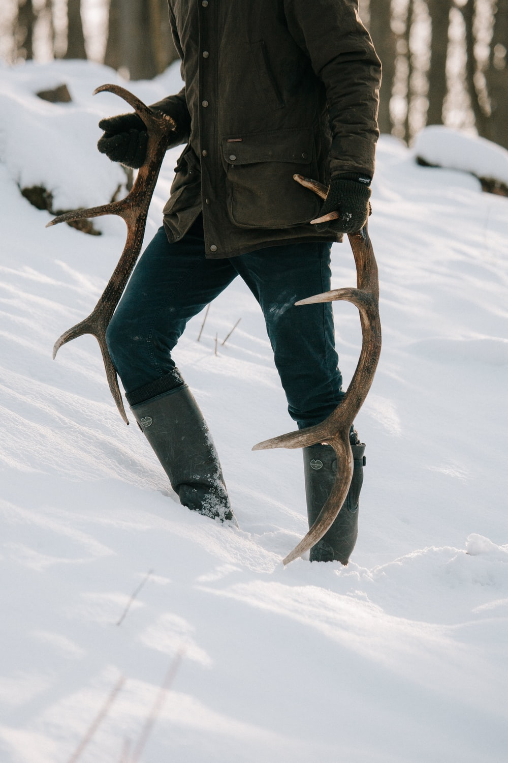 person holding two antlers