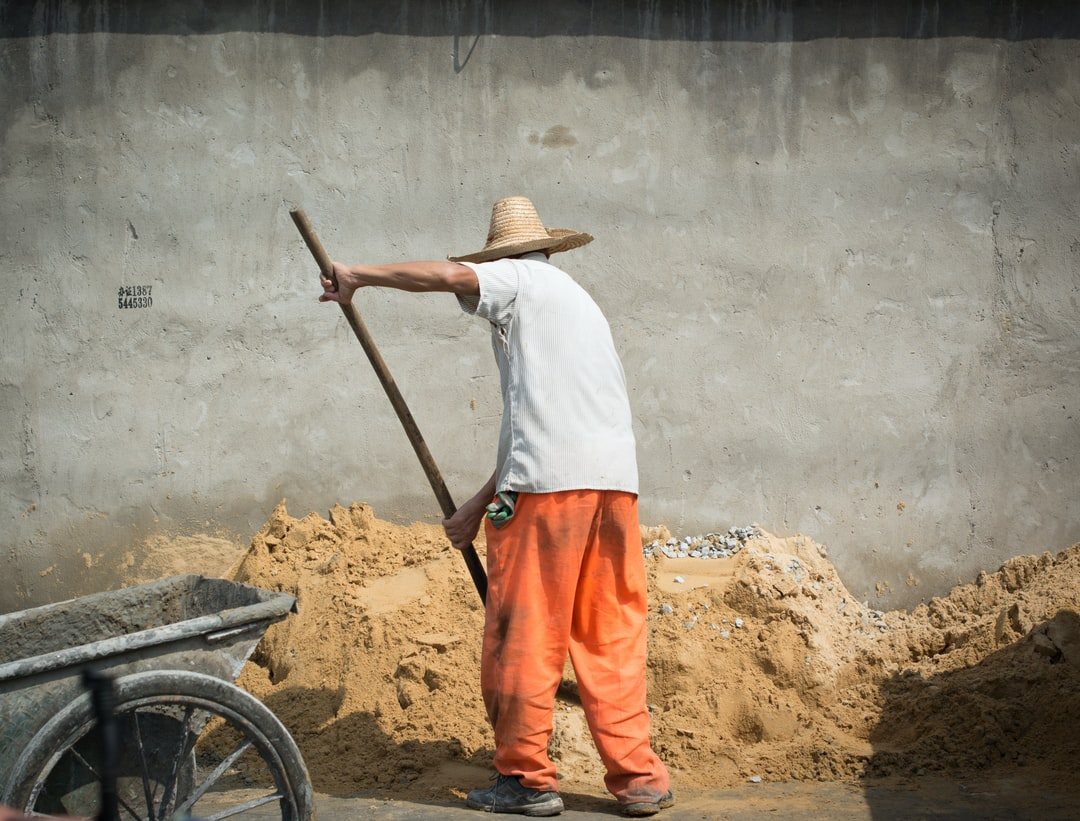 Older man shoveling sand working china