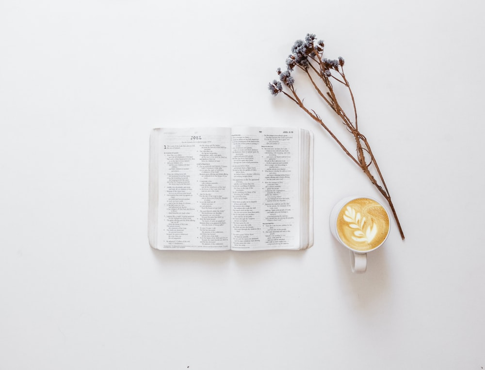 flatlay photo of Bible, flowers, and cup of latte