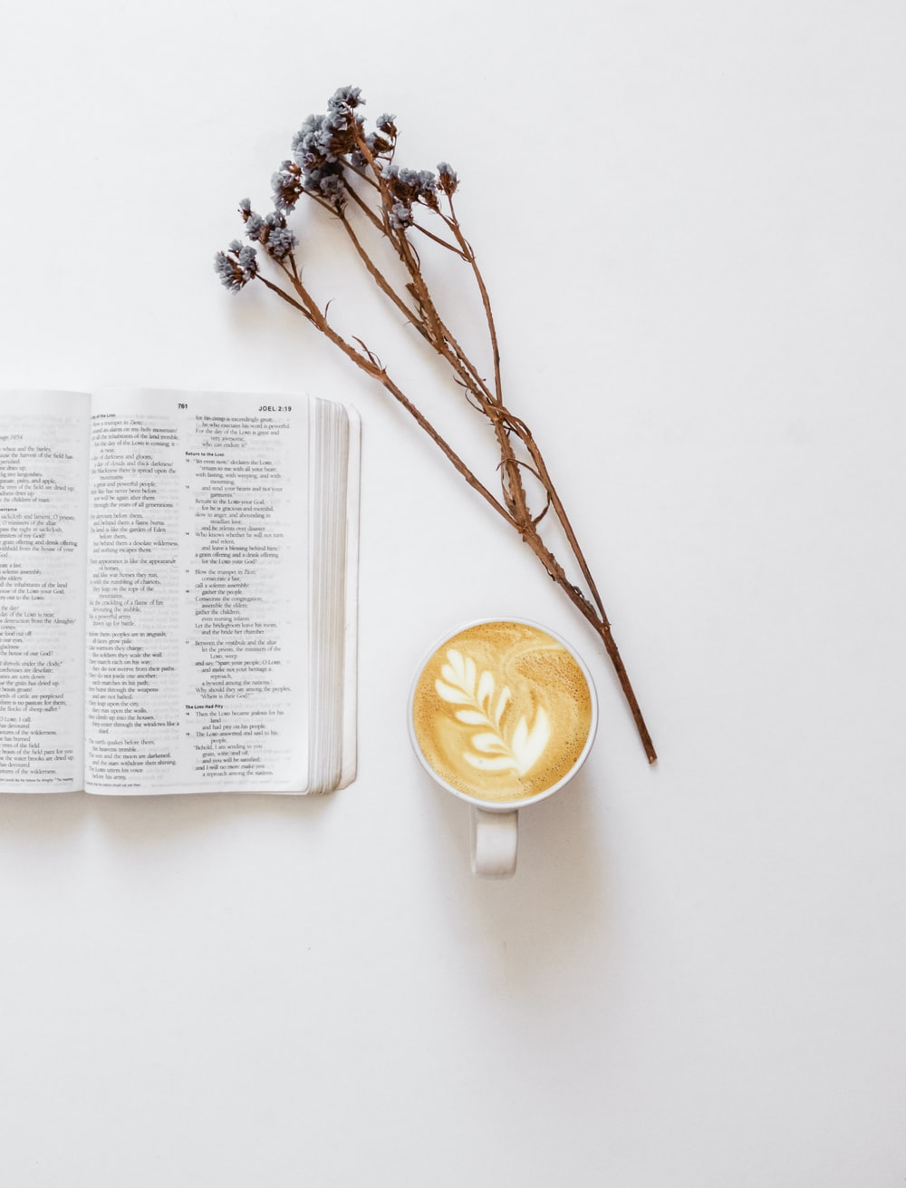 flatlay photo of flowers, bible, and cup of coffee latte