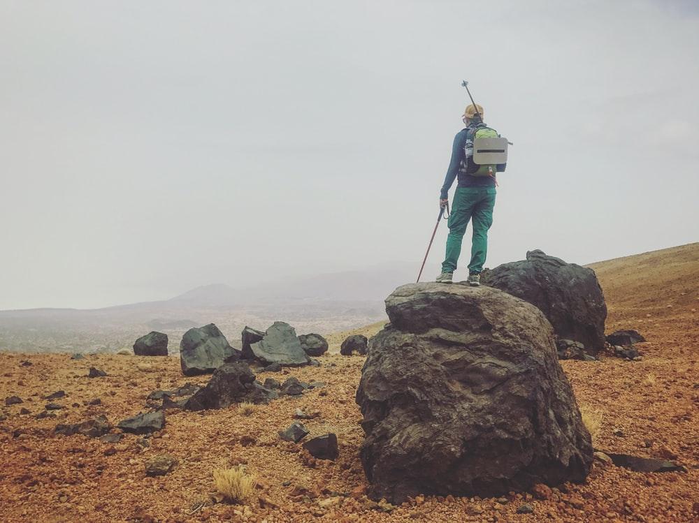 man carrying backpack standing on rock
