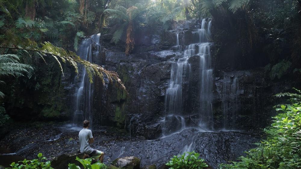 man sitting beside waterfalls