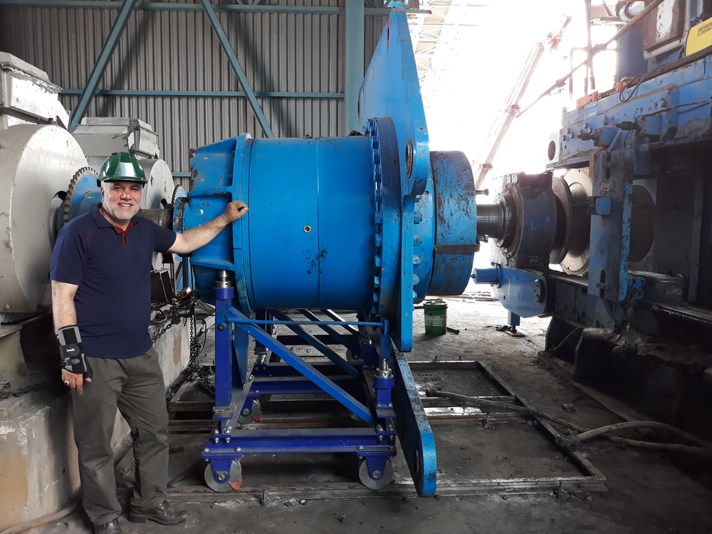 man standing beside a rolling pedestal industrial machine