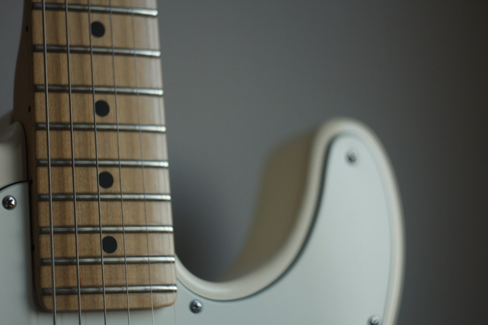 white and brown string instrument close-up photography