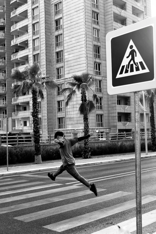 man jumping over pedestrian lane