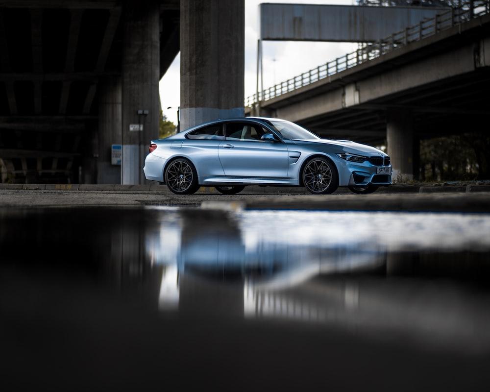 blue coupe under bridge