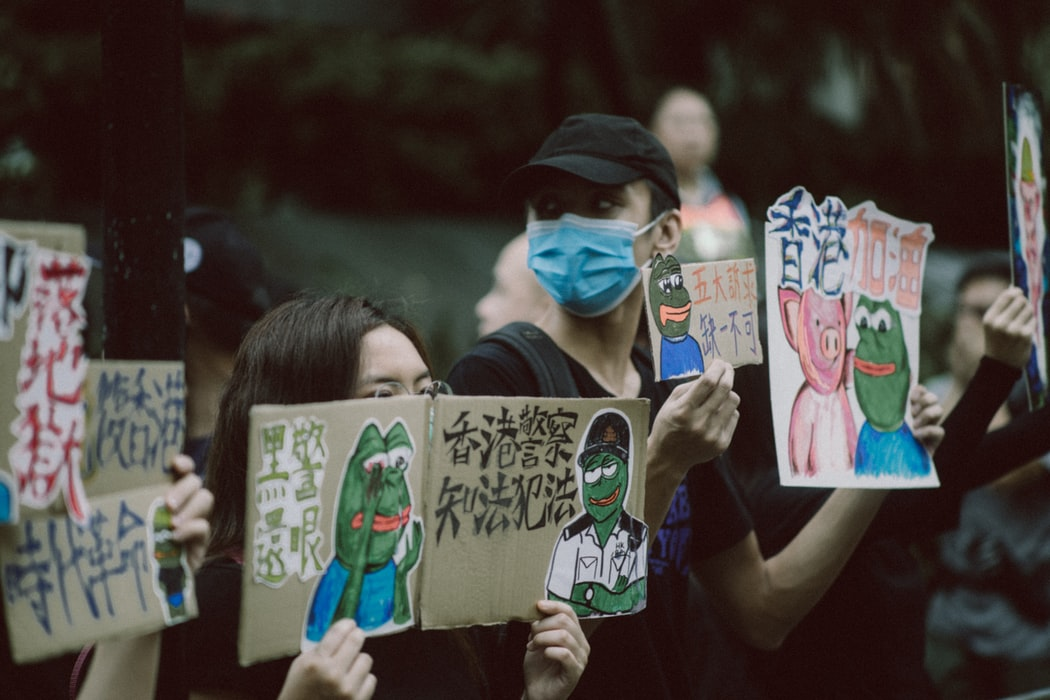 Hong Kong protestors hold signs criticizing police brutality.