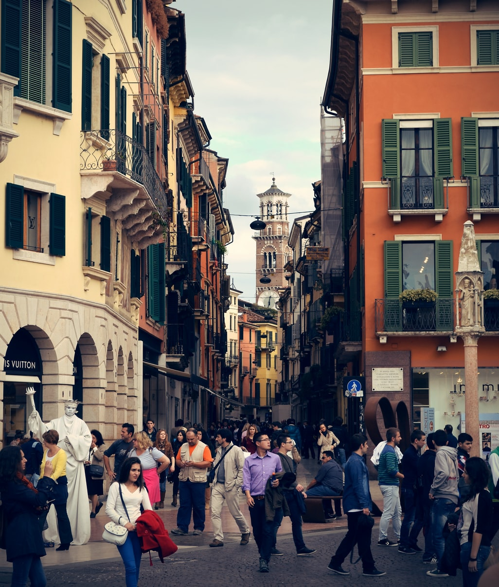 an alleyway with people in Verona, Italy