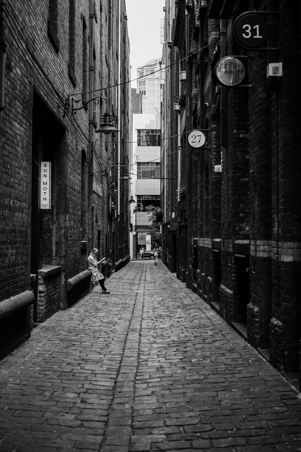 person leaning back on brick building in the alley