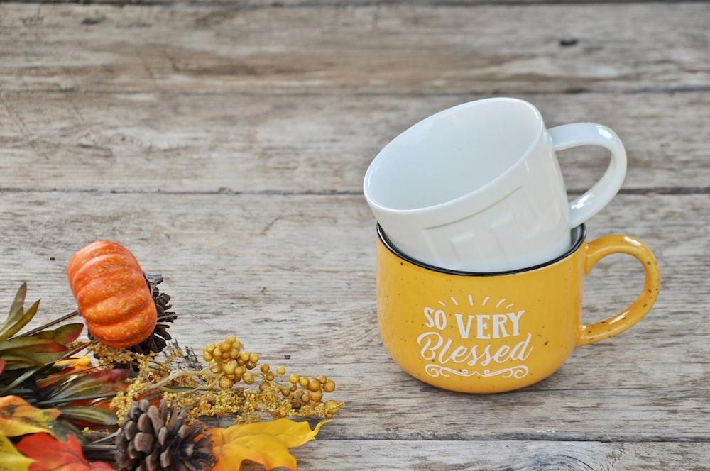 two white and yellow ceramic mugs