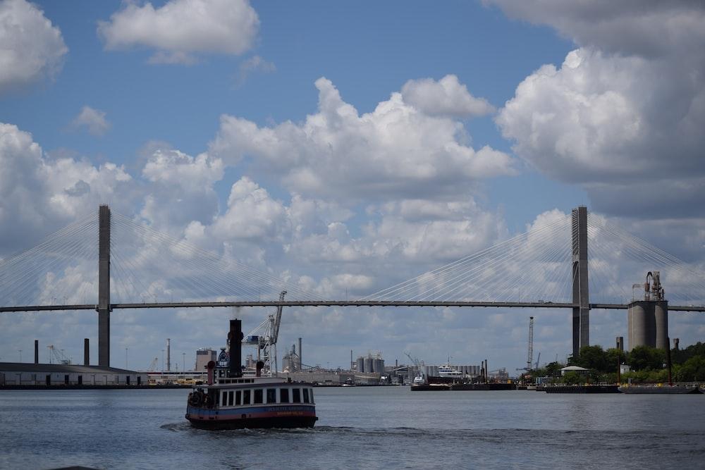 white boat near bridge