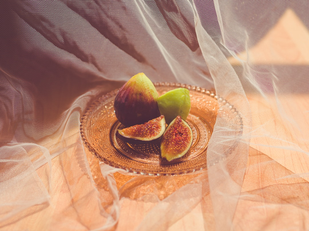 Several ripe figs served on an ornate glass plate behind wispy gauze fabric drapery drenched in sunlight coming through the window.