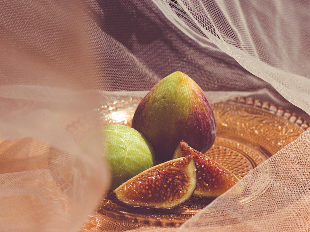 Three ripe figs served on an ornate glass plate behind wispy gauze fabric drapery.