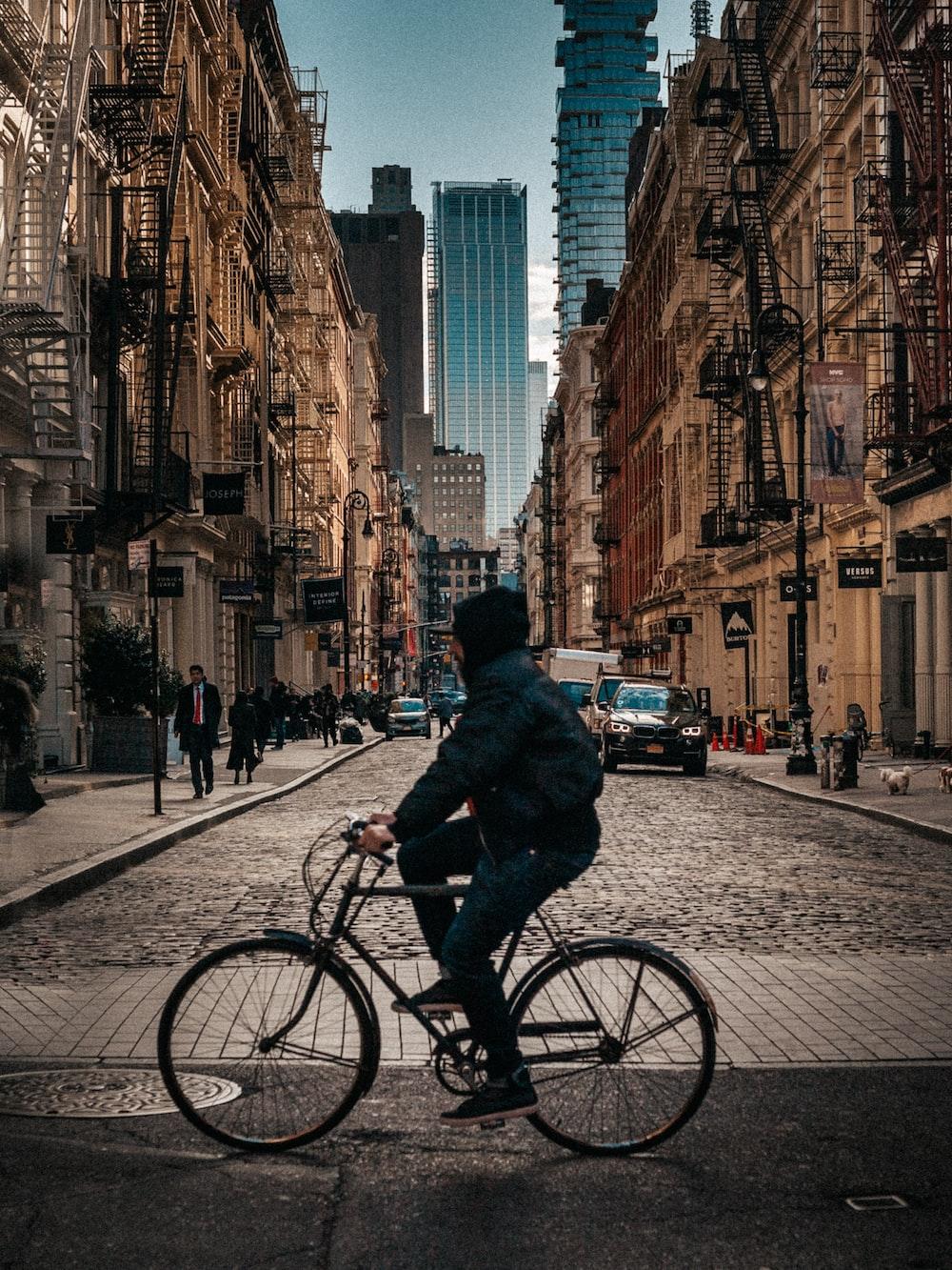man wearing jacket riding on bike