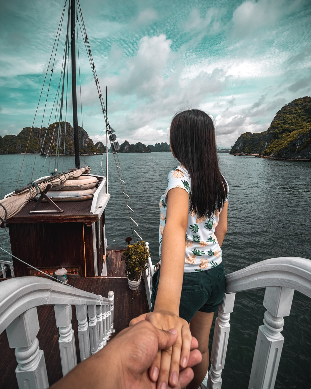 person holding woman's hand looking at body of water under cloudy sky