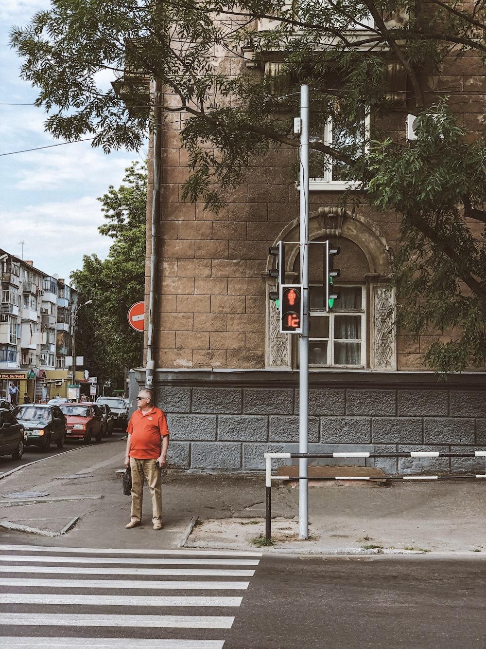 man standing on sidewalk near pedestrian lane