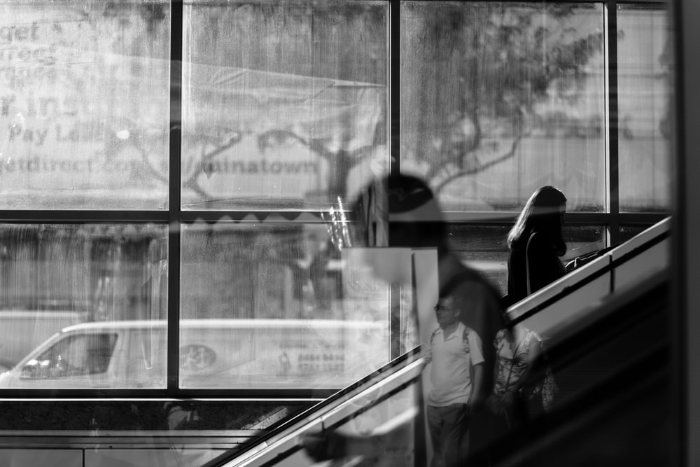 grayscale photo of woman using escalator