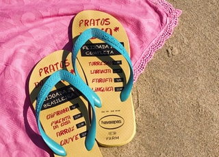 pair of yellow-and-blue havaianas flip-flops on pink textile