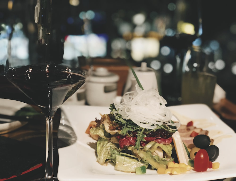 rectangular white plate with foods besides wine glass