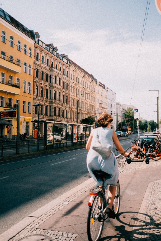 woman riding bicycle near concrete building