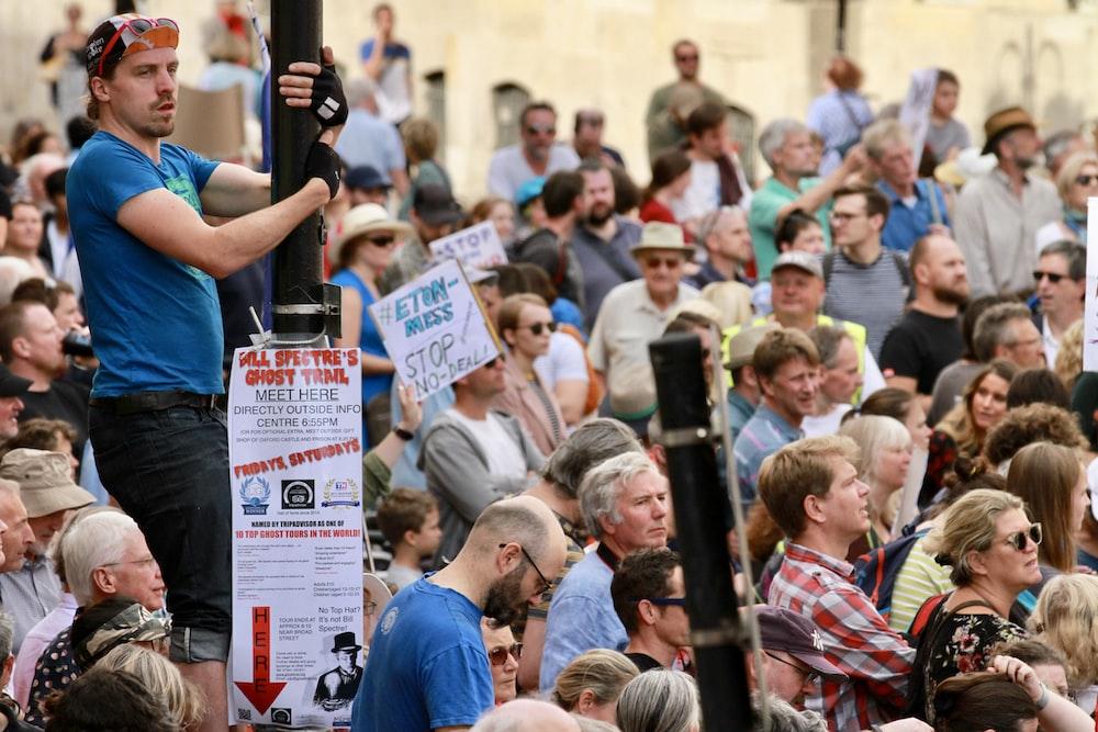 standing man wearing blue crew-neck t-shirt