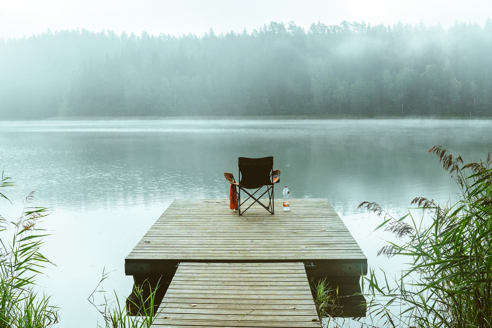 gray wooden dock beside body of water at daytime