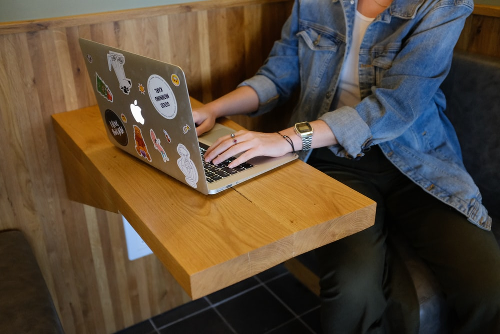 woman sitting and using MacBook