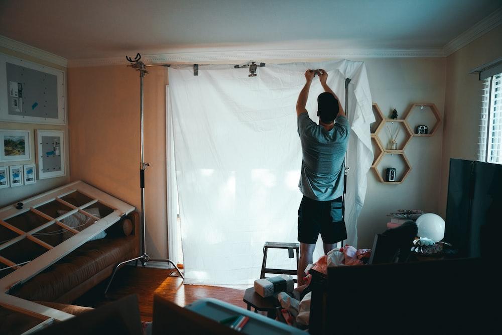 man standing beside white curtain