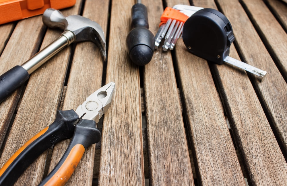 assorted-type carpentry tools on brown surface