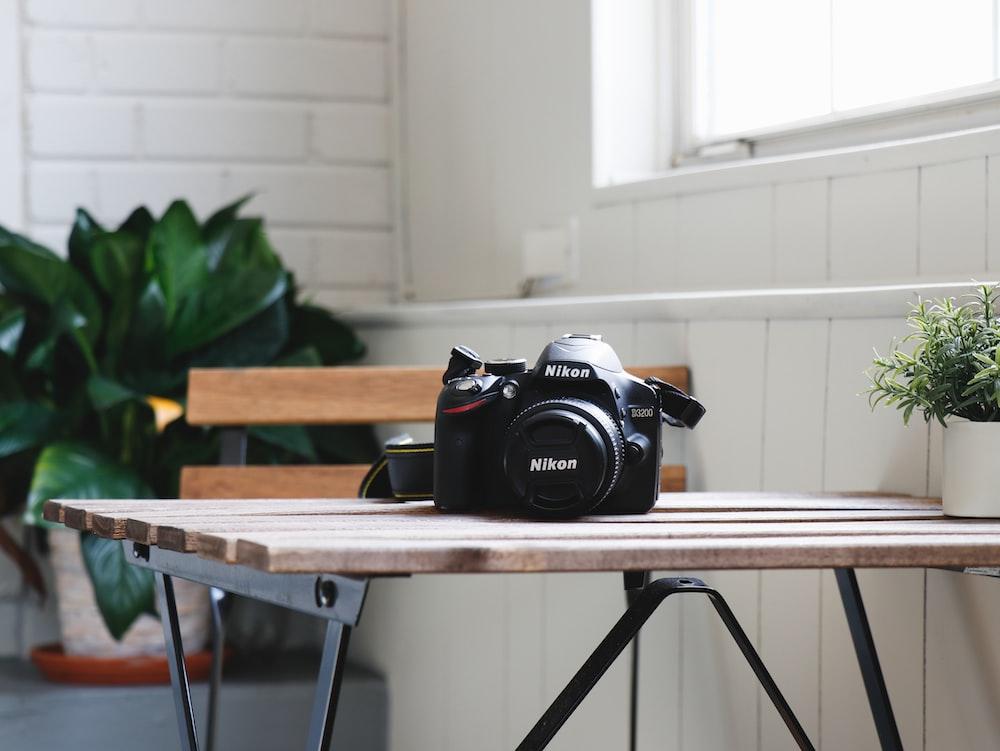 black Nikon DSLR camera on table