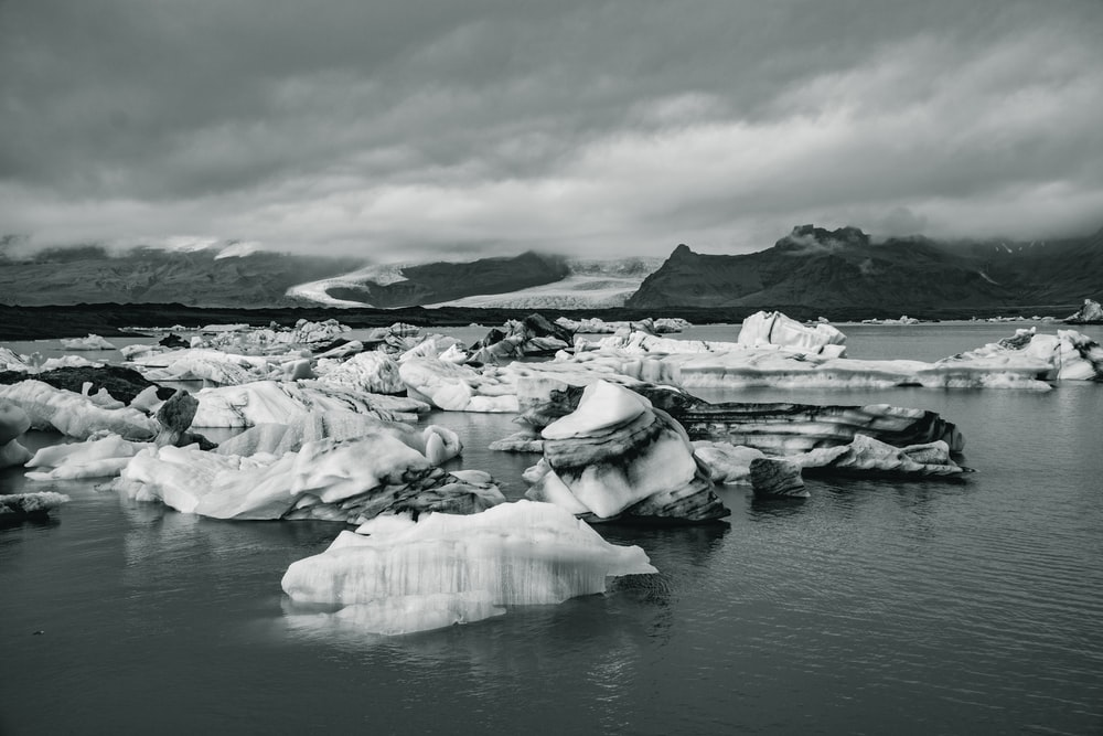 grayscale photography of body of water and mountain