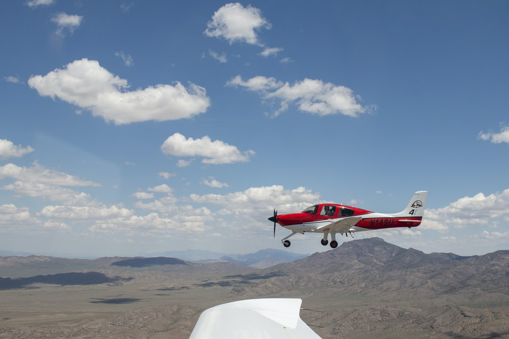 red and white plane on air