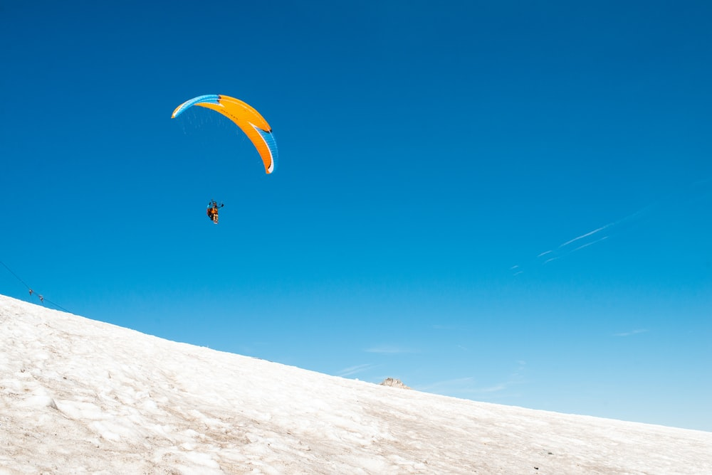 person paragliding in midair during daytime